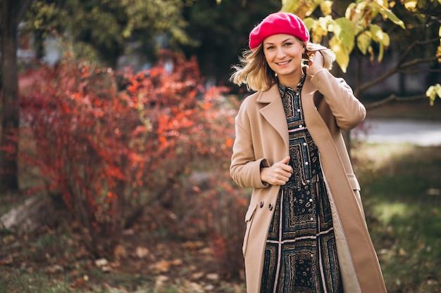 Jolie jeune femme dans un barret rouge à l'extérieur dans le parc