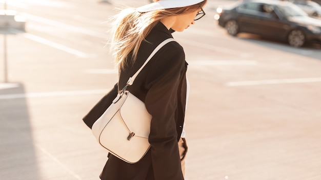 Jolie jeune femme dans un chapeau et des lunettes avec un sac à la mode blanc marchant dans la rue au coucher du soleil. collection d'été de mode de sacs en cuir