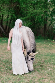 Jolie jeune femme dans une robe blanche, debout sur le pré vert près de beau cheval blanc