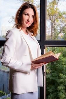 Jolie jeune femme dans une veste blanche d'affaires se tient près de la fenêtre avec un livre dans ses mains