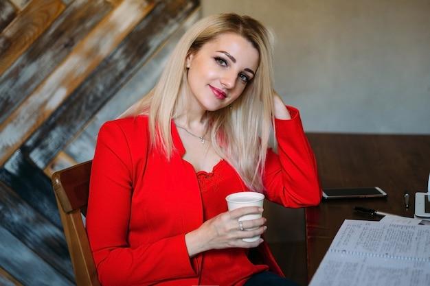 Jolie jeune femme dans une veste rouge travaille à une table avec des papiers et des appareils