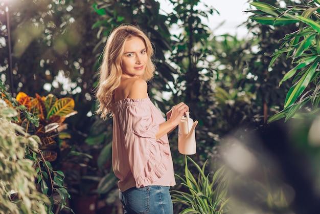 Jolie jeune femme debout dans le jardin tenant un petit arrosoir