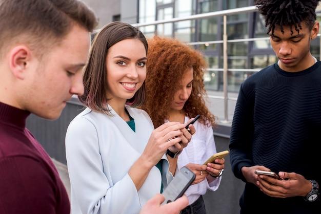 Jolie jeune femme debout entre ses amis à l'aide de téléphones portables en regardant la caméra