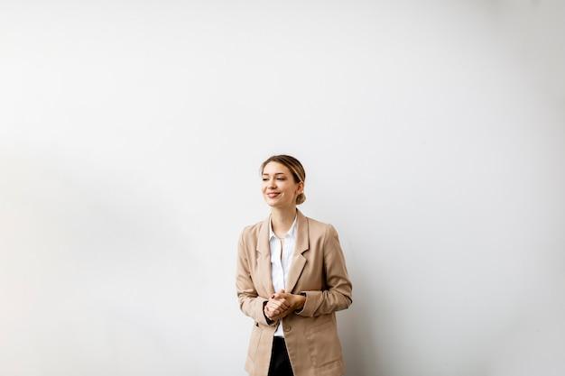 Jolie jeune femme debout près du mur blanc dans un bureau moderne