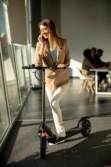 Jolie jeune femme debout près de la fenêtre du bureau avec scooter électrique et à l'aide de téléphone mobile