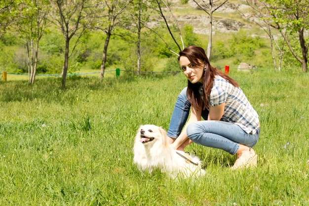 Jolie jeune femme décontractée en jeans se penchant et jouant avec son mignon petit chien à poil long dans l'herbe verte à la campagne