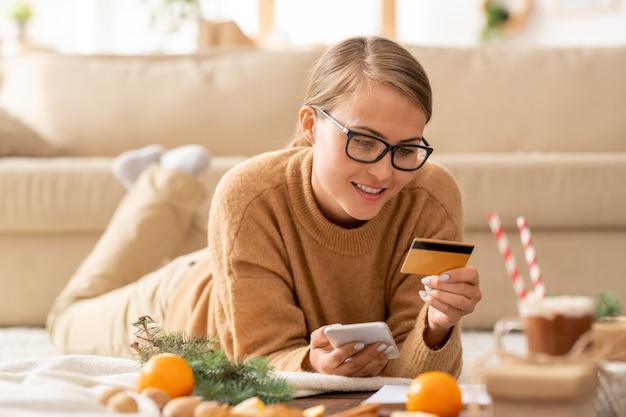 Jolie jeune femme décontractée avec smartphone et carte de crédit à la recherche de données personnelles tout en allant payer pour la commande en ligne