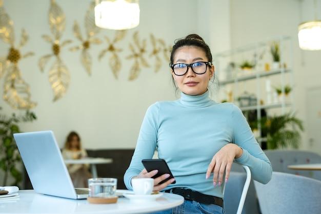 Jolie jeune femme décontractée avec smartphone en vous regardant assis par table devant la caméra dans le café