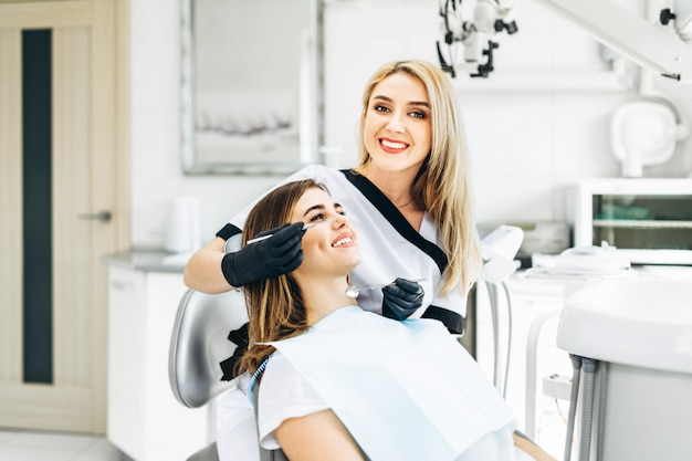 Jolie jeune femme dentiste faisant examen et traitement pour jeune patiente en clinique dentaire.