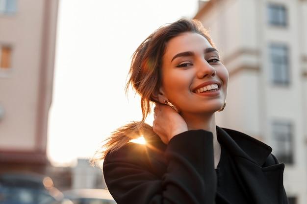Jolie jeune femme drôle dans un t-shirt vintage noir dans un manteau noir à la mode bénéficie d'un coucher de soleil lumineux orange dans la ville près des bâtiments