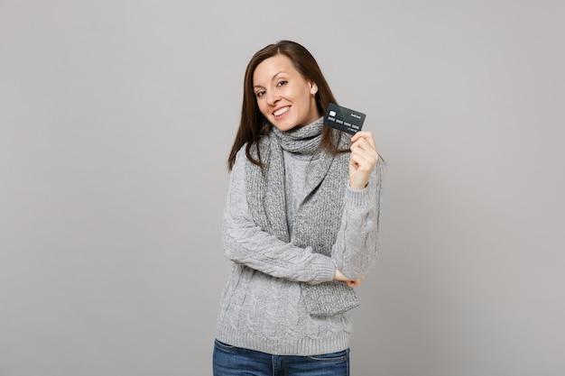Jolie jeune femme en écharpe pull gris tenant une carte bancaire de crédit isolée sur fond gris en studio. gens de mode de vie sain émotions sincères, concept de saison froide. maquette de l'espace de copie.