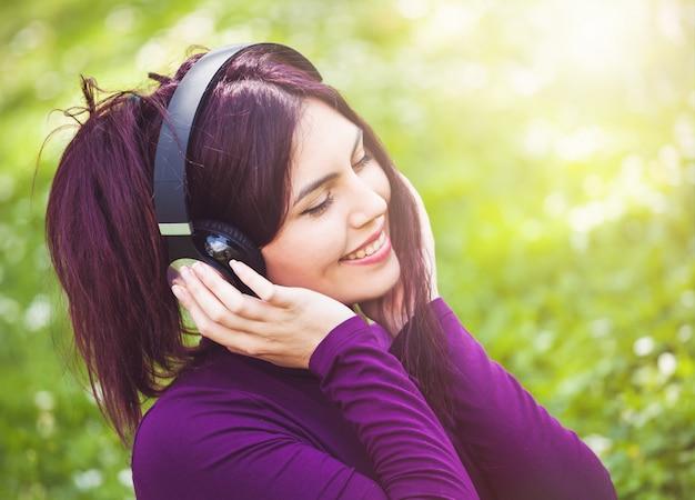 Jolie jeune femme écoutant de la musique avec des écouteurs
