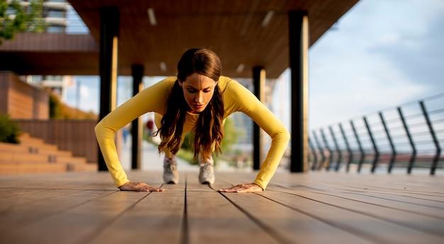 Jolie jeune femme effectuant des pompes sur une passerelle en bois au bord de la rivière