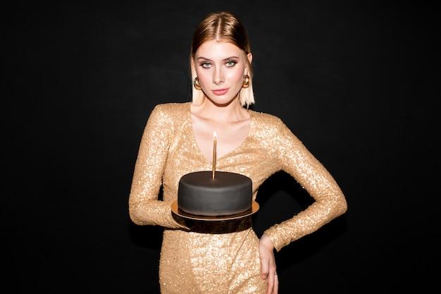 Jolie jeune femme élégante aux cheveux blonds tenant un gâteau d'anniversaire recouvert de massepain noir avec bougie allumée pendant la célébration