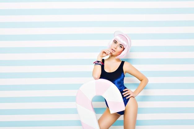 Jolie jeune femme élégante en body bleu reposant sur un mur rayé bleu-blanc. porter une coiffure rose coupée, des talons, un bonnet de plage. modèle sexy, grosse sucette, regardant, humeur joyeuse.