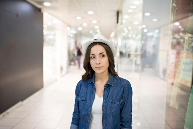 Jolie jeune femme élégante dans un chapeau marche sur le centre commercial pendant le shopping