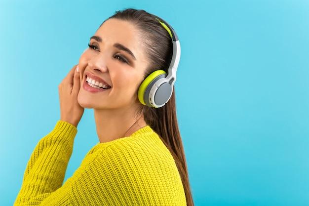 Jolie jeune femme élégante écoutant de la musique dans des écouteurs sans fil heureux portant un pull en tricot jaune style coloré posant