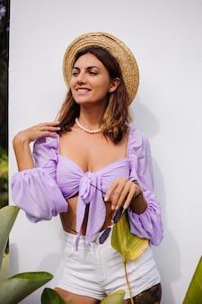 Jolie jeune femme élégante en haut court violet à la mode à manches longues