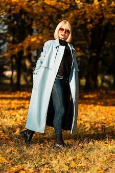 Jolie jeune femme élégante en lunettes de soleil vintage avec un élégant manteau bleu se promène dans un parc d'automne avec un feuillage d'automne jaune par une journée ensoleillée