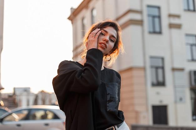 Jolie jeune femme élégante et moderne avec un maquillage naturel avec des lèvres sexy dans un t-shirt à la mode dans un manteau à la mode près des bâtiments vintage à l'extérieur