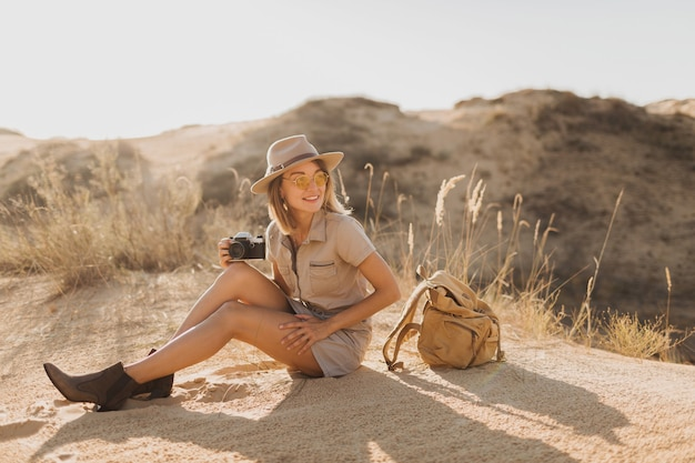 Jolie jeune femme élégante en robe kaki dans le désert, voyageant en afrique en safari, portant un chapeau et un sac à dos, prenant une photo sur un appareil photo vintage