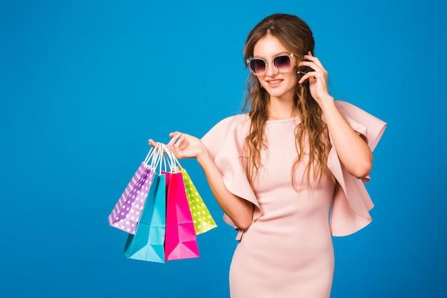 Jolie jeune femme élégante en robe de luxe rose à l'aide d'un téléphone portable et tenant des sacs à provisions