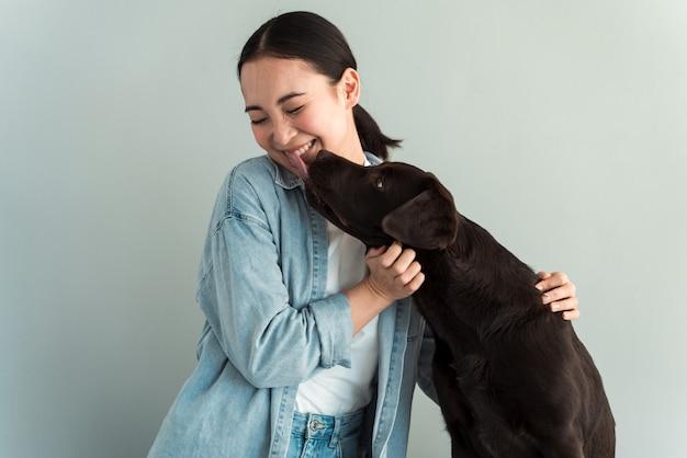 Jolie jeune femme embrasse son chiot labrador chien. un chien embrasse une fille. amour entre chien et maître. isolé sur fond gris. portrait en studio