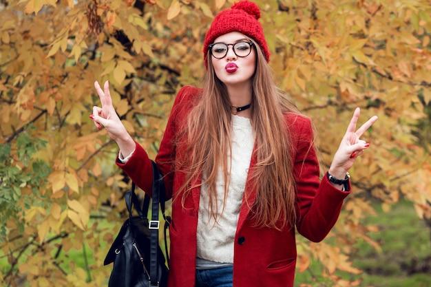 Jolie jeune femme envoie un baiser. jolie dame portant des vêtements d'automne rouges