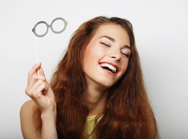 Jolie jeune femme espiègle avec de fausses lunettes