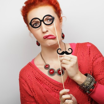 Jolie jeune femme espiègle tenant la moustache et les lunettes sur un bâton. prêt pour la fête.