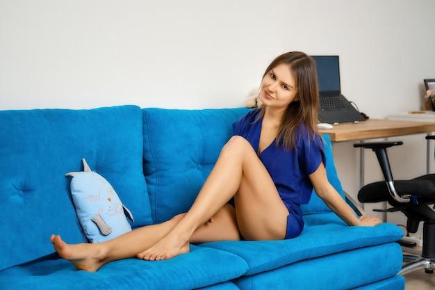 Jolie jeune femme est assise sur un canapé bleu à la maison