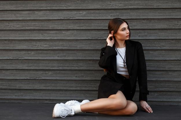 Jolie jeune femme est assise près d'un mur en bois