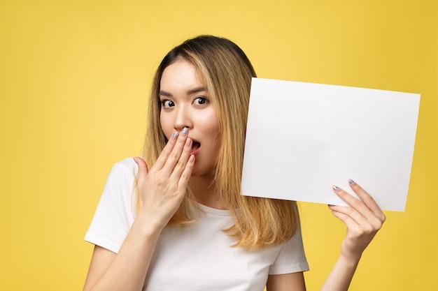 Jolie jeune femme étudiante asiatique belle tenant du papier blanc vierge