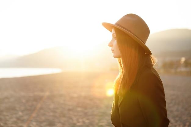 Jolie jeune femme européenne pensive portant des vêtements chauds élégants se détendre au bord de la mer