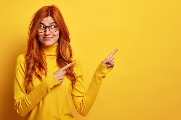 Jolie jeune femme européenne rousse avec une expression joyeuse indique à un espace vide suggère de suivre cette direction porte un col roulé décontracté.