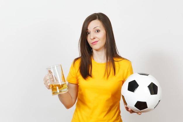 Une jolie jeune femme européenne triste, un fan de football ou un joueur en uniforme jaune tient une chope de bière, s'inquiète de perdre l'équipe isolée sur fond blanc. sport, jouer au football, concept de style de vie.