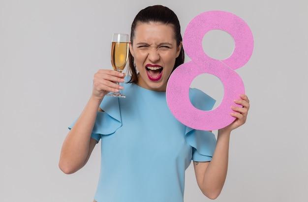 Jolie jeune femme excitée tenant le numéro rose huit et une coupe de champagne