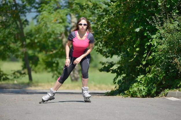 Jolie jeune femme faisant du roller sur une piste