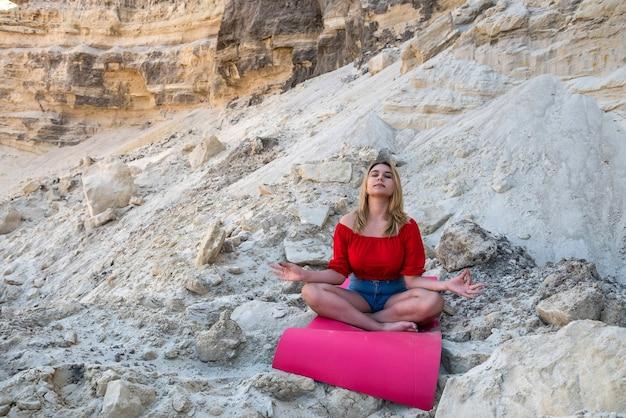 Jolie jeune femme faisant de l'exercice de yoga relax avec tapis sur sable sec entre carrière vide
