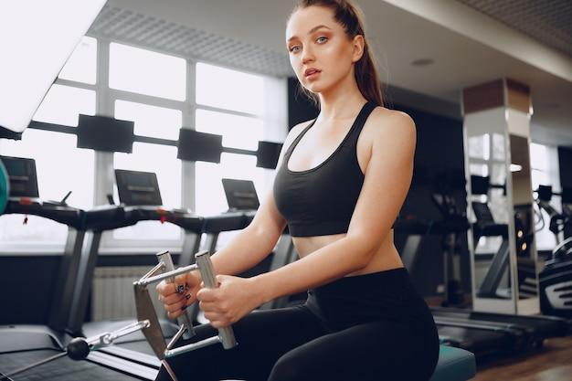 Jolie jeune femme faisant des exercices pour les muscles des bras et du dos dans une salle de sport