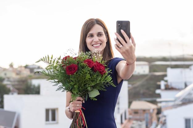 Jolie jeune femme faisant un selfie avec un bouquet de roses rouges