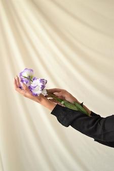 Jolie jeune femme sur fond beige tenant une fleur blanche
