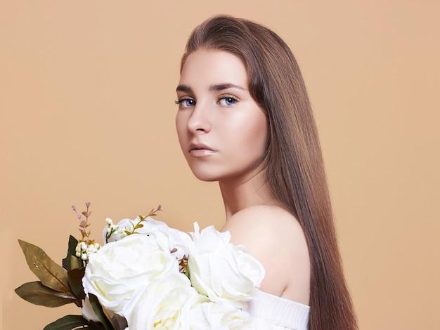 Jolie jeune femme sur fond blanc. portrait d'une belle fille avec un bouquet de fleurs blanches.