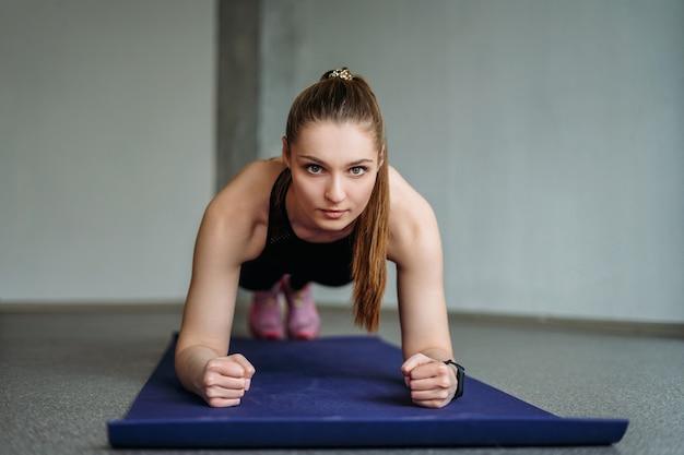 Jolie jeune femme en forme de vêtements de sport fille trains avec des haltères font planche au studio loft