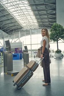 Jolie jeune femme gardant le sourire sur son visage tout en se préparant pour le vol, étant heureuse pour le début des vacances