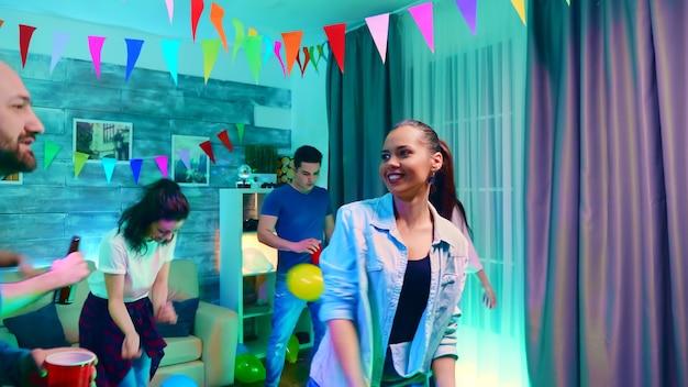 Jolie jeune femme avec un grand sourire plein d'excitation faisant la fête avec ses amis.