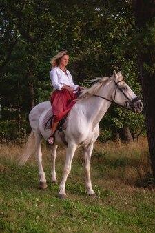 Jolie jeune femme heureuse à cheval dans un parc d'été. la femelle du cavalier conduit son cheval dans le parc sur la nature sur fond clair du coucher du soleil du soir. concept d'équitation en plein air, de sports et de loisirs. espace de copie