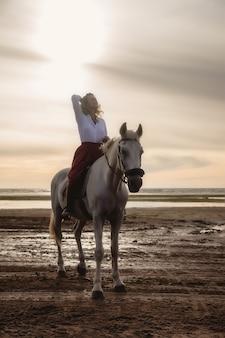 Jolie jeune femme heureuse à cheval sur la plage d'été au bord de la mer. la femelle du cavalier conduit son cheval dans la nature sur fond clair du coucher du soleil du soir. concept d'équitation en plein air, de sports et de loisirs. espace de copie