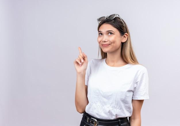 Une jolie jeune femme heureuse en t-shirt blanc portant des lunettes de soleil sur sa tête en levant l'index tout en ayant une suggestion sur un mur blanc