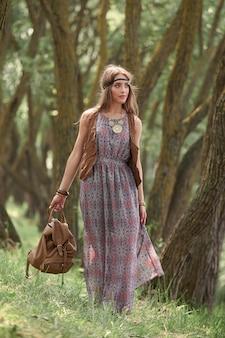 Jolie jeune femme hippie marchant parmi les arbres en forêt. le concept d'unité avec la nature